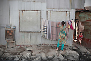 A woman hangs some blankets on the side of her metal walled home as a youngster runs from the 'street'.  The slum of Cheetah Camp on the outskirts of Mumbai, India is a predominantly muslim community on living on the fringe while the city continues to grow.