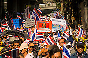 """15 JANUARY 2014 - BANGKOK, THAILAND:  Anti-government protestors follow Suthep Thaugsuban up Sukhumvit Road during a protest march in Bangkok Wednesday. Tens of thousands of Thai anti-government protestors continued to block the streets of Bangkok Wednesday to shut down the Thai capitol. The protest, """"Shutdown Bangkok,"""" is expected to last at least a week. Shutdown Bangkok is organized by People's Democratic Reform Committee (PRDC). It's a continuation of protests that started in early November. There have been shootings almost every night at different protests sites around Bangkok. The malls in Bangkok are still open but many other businesses are closed and mass transit is swamped with both protestors and people who had to use mass transit because the roads were blocked.   PHOTO BY JACK KURTZ"""