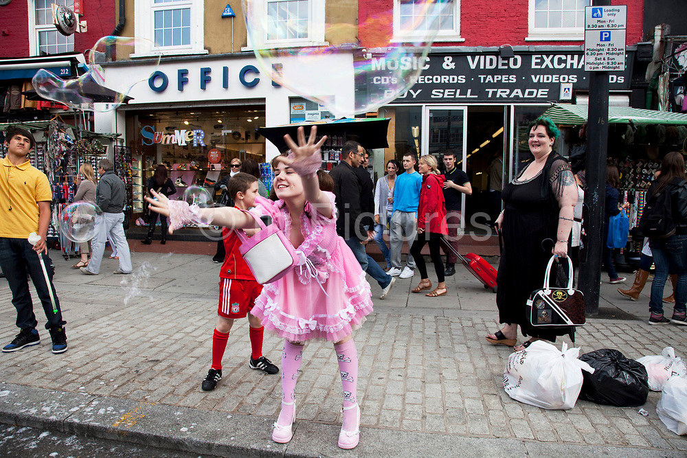 Mother Louise Irwin-Ryan with her daughter Georgia (11, wearing a pink Lolita dress) and son Kiefer (8, wearing a red Liverpool Football Club kit) spending a day out together in Camden Town, North London. The kids here both decide to play on the side of the road trying to burst giant bubbles. Louise is on various benefits to help support her family income, and housing, although recent government changes to benefits may affect her family drastically, possibly meaning they may have to move out of London. Louise Ryan was born on the Wirral peninsula in 1970.  She moved to London with her family in 1980.  Having lived in both Manchester and Ireland, she now lives permanently in North London with her husband and two children. Through the years Louise has battled to recover from a serious motorcycle accident in 1992 and has recently been diagnosed with Bipolar Affective Disorder. (Photo by Mike Kemp/For The Washington Post)