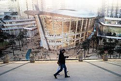 couple walking past large billboard showing proposed new Opera House under construction in Downtown Dubai United Arab Emirates