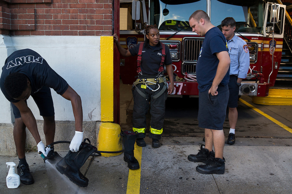 Firefighter Melissa Bennett, center, watches as a fellow fighter decontaminates his equipment after a run at the quarters of Engine 257, 1361 Rockaway Parkway, Brooklyn, NY on Tuesday, Oct. 6, 2015.<br /> <br /> Andrew Hinderaker for The Wall Street Journal<br /> NYFDNY