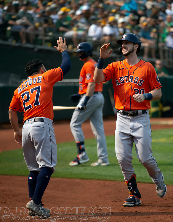 Sep 25, 2021; Oakland, California, USA; Houston Astros right fielder Kyle Tucker (30) gets a high five from teammate Jose Altuve (27) after hitting a solo home run against the Oakland Athletics during the seventh inning at RingCentral Coliseum. Mandatory Credit: D. Ross Cameron-USA TODAY Sports
