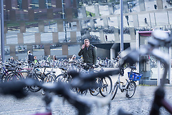 Young student standing outside parking lot with bicycle and talking on mobile phone, Freiburg im Breisgau, Baden-Wuerttemberg, Germany