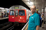 London Underground Circle Line tube train approaches the station at Embankment. Passenger stand behind the yellow safety line.