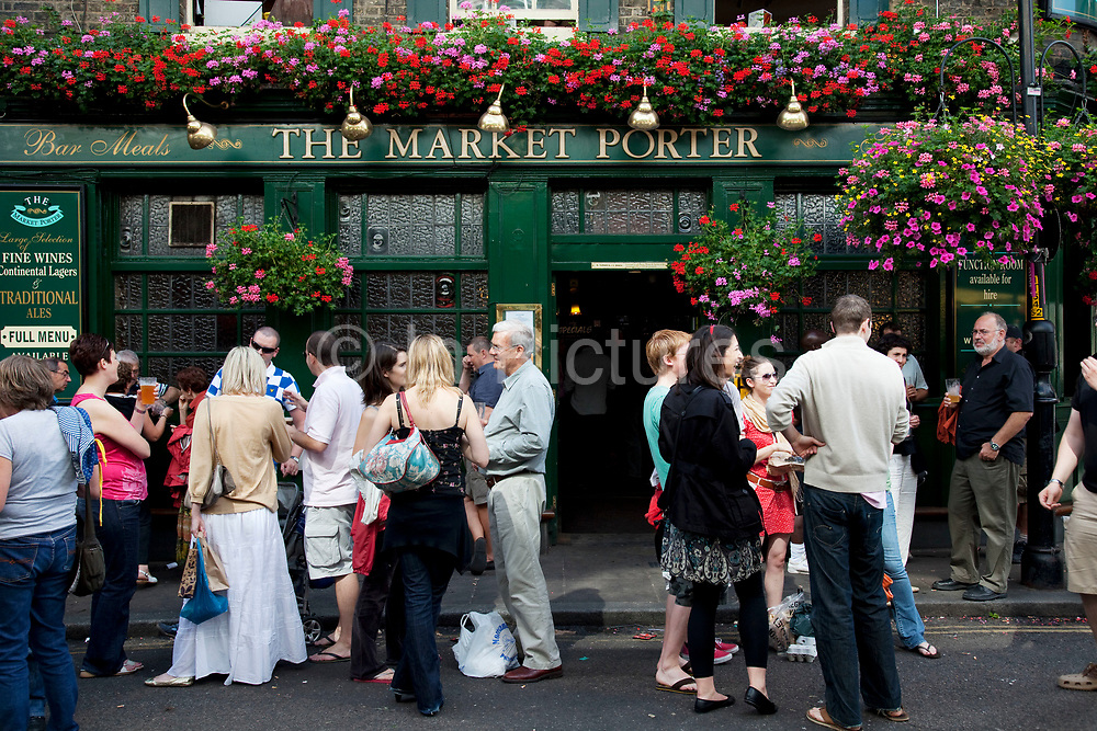 Drinkers stand outside the Market Porter pub, a popular place for friends to gather. Borough Market is a thriving Farmers market near London Bridge. Saturday is the busiest day.