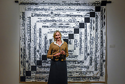 "© Licensed to London News Pictures. 26/02/2020. LONDON, UK. Artist Cath Kidston poses with Ai Wei Wei's ""Odyssey in Quilting"", 2019 (Starting price GBP70,000).  Preview of ""Human Touch"", an exhibition of one-of-a-kind artworks by international contemporary artists in collaborations with stitchers in British prisons.  In association with the charity Fine Cell Work, the artworks are on show at Sotheby's New Bond Street 26 February to 3 March 2020.  Photo credit: Stephen Chung/LNP"