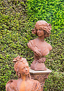 Rusted metal cast iron bust statues female figures, The Walled garden plant nursery, Benhall, Suffolk, England, UK