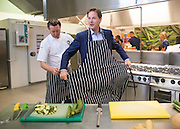 © Licensed to London News Pictures. 02/09/2014. London, UK. Nick Clegg prepares to chop vegetables in the school's kitchen. Deputy Prime Minister Nick Clegg launches free school meals at Clapham Manor Primary School in Lambeth today 2nd September 2014. For many school returning from the school holidays this is the first day of the Governments universal infant free school meals.  Photo credit : Stephen Simpson/LNP