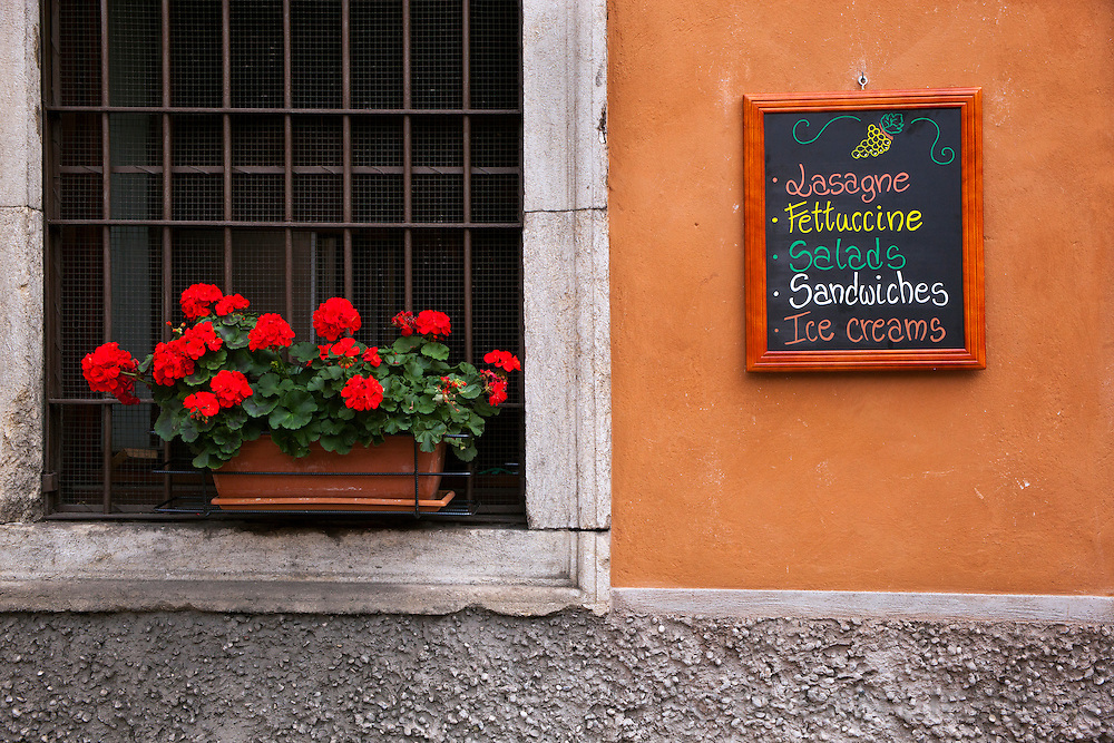 A sign with food items listed and a flower box in Verona, Italy.