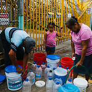 Residents fill containers of water at a water oasis located in Rio Grande, Puerto Rico., on Thursday, October 3, 2017. John Taggart/Bloomberg