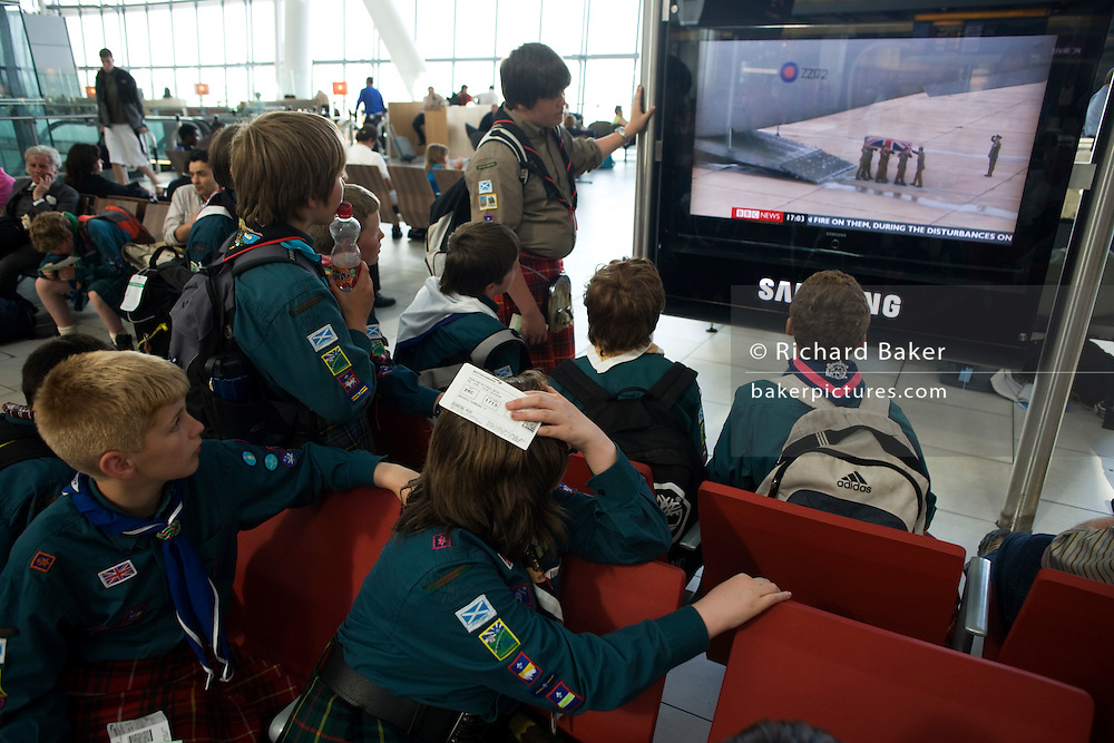Scottish scout troupe passengers watch sad TV news while awaiting their flight in departures at Heathrow's Terminal 5.