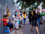 24 MARCH 2017 - BANGKOK, THAILAND: People walk by a vendor selling coconut water on Sukhumvit Road near Soi 69 (Phra Khanong). The coconut water vendor and the food carts behind her have to leave the area by 17 April. Food cart vendors along Sukhumvit Road between Sois 55 (Thong Lo) and 69 (Phra Khanong) in Bangkok have been told by city officials that they have to leave the area by 17 April. It's a part of an effort by Bangkok city government, supported by the ruling junta, to take back the city's sidewalks. The evictions in the area are the latest in mass evictions of Bangkok street food vendors after similar actions elsewhere on Sukhumvit, in the Ari area, in Silom/Patpong and Ratchaprasong neighborhoods. The vendors in Thong Lo/Phra Khanong are popular with local office workers because most of the formal restaurants in the area serve foreign tourists and upper class Thais and are very expensive. The street food carts serve meals starting at about 35Baht ($1US). The city has not announced if they will provide alternative locations for the carts.     PHOTO BY JACK KURTZ