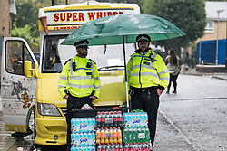 © Licensed to London News Pictures. 26/08/2018. London, UK. Police officers shelter form the wet and windy conditions at family day of the 2018 Notting Hill Carnival. Up to 1 million people are expected to attend this weekend's event that is one of the worlds largest street festivals. Photo credit: Ben Cawthra/LNP