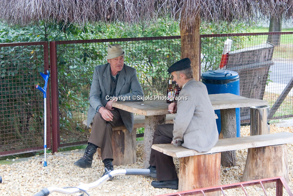 Two gentlemen having beers at a table in the grocery store courtyard.  Sadykierz   Central Poland