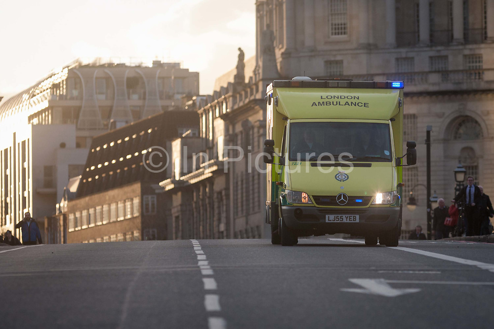 Ambulance crossed Lambeth Bridge, closed in the aftermath of the terrorism event when four people were killed including the attacker and 20 injured during a terrorist attack on Westminster Bridge and outside the Houses of Parliament, on 22nd March 2017, in central London, England. Parliament was in session and all MPs and staff and visitors were in lock-down while outside, the public and traffic were kept away from the area of Westminster Bridge and parliament Square, the scenes of the attack. It is believed a lone man crashed his car into pedestrians then, armed with a knife tried to enter Parliament, stabbing and killing a police officer at parliaments main gates.