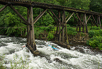 """A kayaker navigates the trestle during """"Winni River Days"""" whitewater festival in Franklin on Saturday.  (Karen Bobotas/for the Laconia Daily Sun)"""