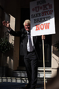 A man dressed like Boris Johnson helds a protestsign with the text For UK's sake stop Brexit now