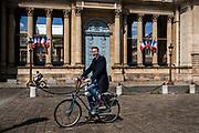 """Stein van Oosteren bikes in front of the Assemblée Nationale in Paris.  He is the author of the book """"Pourquoi pas le velo"""" and  president of bicycle association near Paris.,   Paris, France, May 7, 2021.<br /> Stein van Oosteren sur son vélo devant l'Assemblée Nationale à Paris. Il est l'auteur du livre """"Pourquoi pas le vélo"""" et président de l'association cycliste Faravelo près de Paris. Paris, France, 7 mai, 2021."""