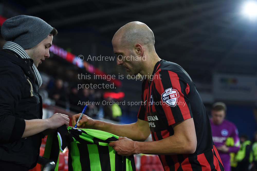 Bruno Saltor of Brighton signs a fans shirt at end of the match. Skybet football league championship match, Cardiff city v Brighton & Hove Albion at the Cardiff city Stadium in Cardiff, South Wales on Tuesday 10th Feb 2015.<br /> pic by Andrew Orchard, Andrew Orchard sports photography.