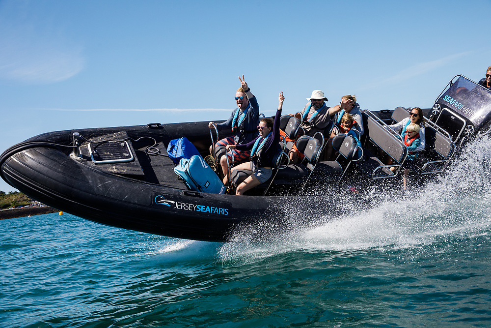 Tourists and friends out on a Seafaris boat excursion, speeding around the harbour in Jersey, Channel Islands in summer
