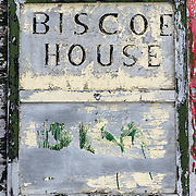 A sign for Biscoe House amongst the ruins at the abandoned whaling station at Whalers Bay, Deception Island. Because of the cold temperatures, wood takes much longer to decompose than it does in warmer climates. Deception Island, in the South Shetland Islands, is a caldera of a volcano and is comprised of volcanic rock.