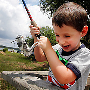 Jethro Dombkowski, of Bluffton, 3, reels in his lure with the help of his father Anthony Dombkowski, not pictured, while out fishing in Pigeon Point Creek on the docks of Roger Pinckney, X Park in Beaufort on June 29, 2014.