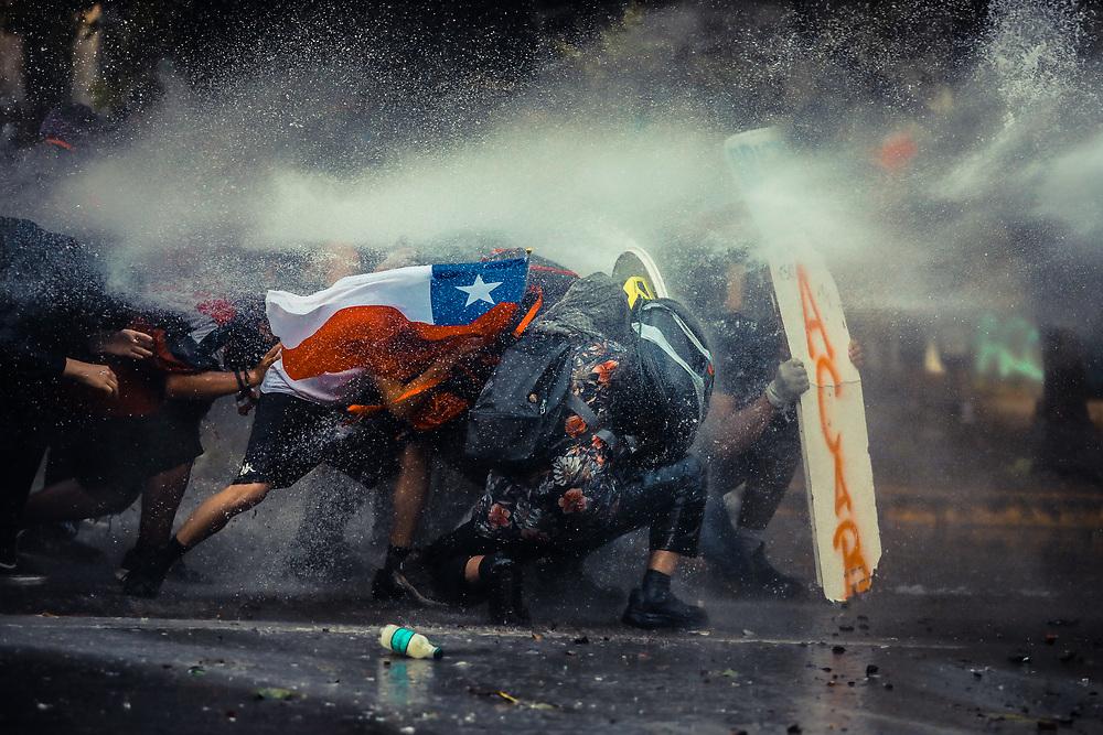 Manifestantes se protegen con un escudo improvisado del agua con químicos utilizada por las Fuerzas Especiales de la Policía durante las protestas en Chile, todo esto a raíz de las manifestaciones comenzadas el 18 de Octubre del mismo año en contra del Gobierno y las políticas utilizadas durante años a los ciudadanos desde el retorno a la democracia en el país.<br /> 11 de Noviembre, Santiago Chile<br /> FOTO: JAVIER VERGARA
