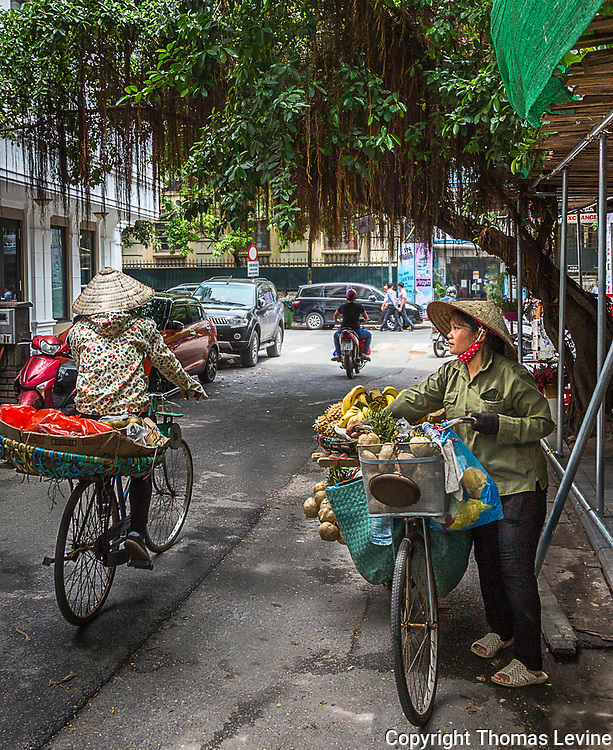 Two bicycle street vendors in Hanoi's Old Quarter pass by each other. RAW to Jpg