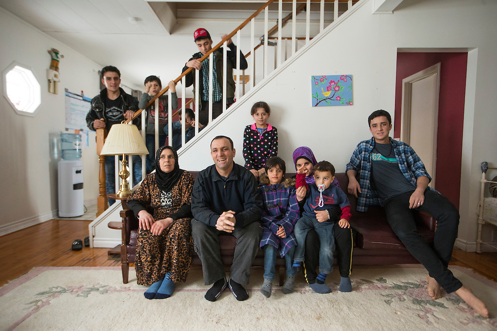 The inside Al Jasem family pose for a picture starting left to right on the couch, Mother Sawsan and father Abdel Malek, their kids, Walaa, Alaa, Khitam, Fadl, and Ramaz, and standing on the staircase left to right, Sleiman Abdel Malek, Madjid, Bachar, and Ahmad, inside their temporary home in Picton, Ontario, Canada, Wednesday January 20, 2016.   (Mark Blinch for the BBC)