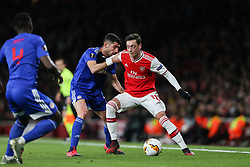 Mesut Ozil of Arsenal holds off a challenge from Andreas Bouhalakis of Olympiacos - Mandatory by-line: Arron Gent/JMP - 27/02/2020 - FOOTBALL - Emirates Stadium - London, England - Arsenal v Olympiacos - UEFA Europa League Round of 32 second leg