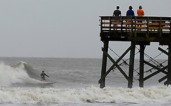 Boys, right, watch a surfer ride a wave near a pier on Oct. 7, 2016 at the Isle of Palms, S.C. Hurricane Matthew is scheduled to skirt the coast of South Carolina later Friday or early Saturday morning.Photo by Jeff Siner/Charlotte Observer/TNS/ABACAPRESS.COM