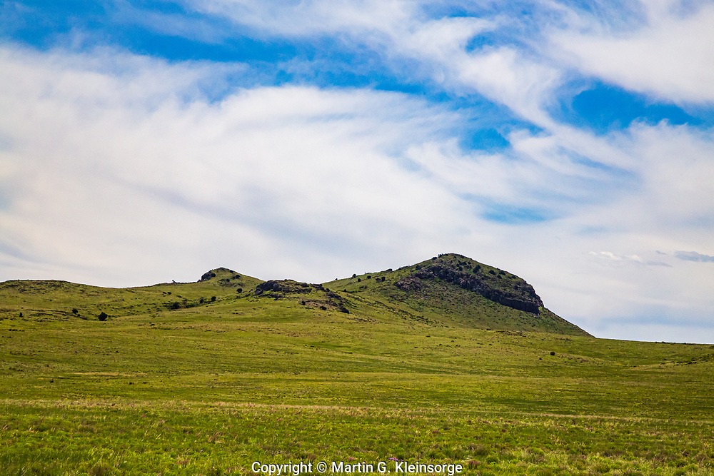 The west side of 6,058 ft. Rabbit Ear Mountain.  The mountain is a remnant of a cinder cone volcano.  Local legend credits the name to a Cheyenne or Comanche chief allegedly killed in battle and buried in a secret cave on the mountain.  Northeast New Mexico.  USA