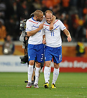 Football - 2010 FIFA World Cup - Netherlands vs. Cameroon<br /> John Heitinga and Arjen Robben of the Netherlands celebrate their win and qualification to the second round top of their group at the final whistle at Green Point Stadium, Cape Town