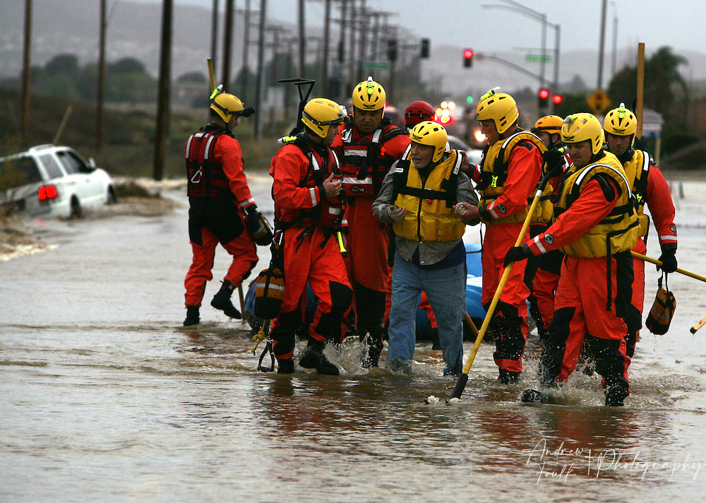 /Andrew Foulk/ For The Californian/ .Menifee Firefighters from station 76 pull help a man form a rescue boat and walk him down a flooded Newport Rd on his way to an awaiting ambulance after he was rescued form his SUV when it was washed off Newport rd just East of La Ladera. The man had to be placed into a rescue boat do to concerns about the mans health and speed of the waters flow.