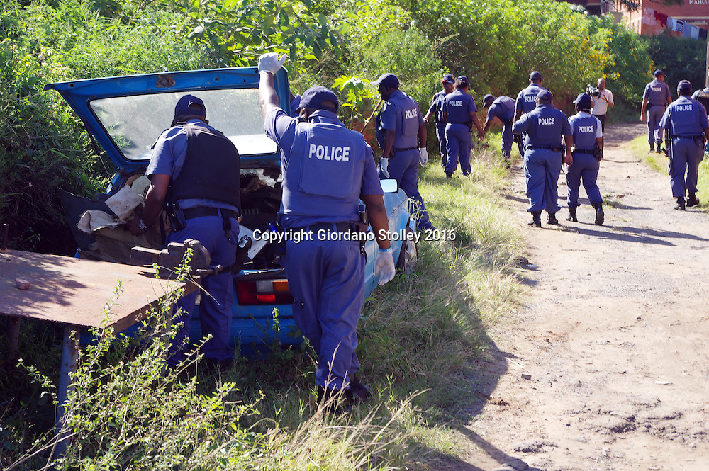 DURBAN - 13 May 2016 - Two police officers inspect a car at Bock R in the Glebelands Hostel to ensure it is not stolen, while their colleg search ground ahed for spent cartridges. They were looking for weapons, drugs and stolen goods. Hundreds of police officers from Durban, the KwaZulu-Natal south coast, Pretoria and the eThekwini Metro Police forces converged on the violent Glebelands Hostels on the edge of Durban's Umlazi township, which have seen numerous shootings that have leftt at least 61 people dead and scores injured. Picture: Allied Picture Press/APP