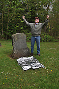 """Humorous photograph of a man successfully covering a grave plot with aluminium foil visually depicting the saying """"The plot is foiled!"""""""
