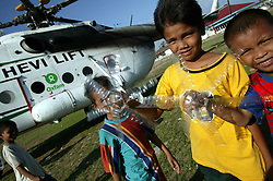 Boys Ibrahim in vertical stripes, Iswadi in yellow, Ikmal in red and blue (I am not absolutely sure of these names, sorry) have used empty plastic bottles and cut them to imitate the blades of the helicopters that lady regularly on the old sports ground in Muelaboh town. <br />In the background is one of the Oxfam Heavy Lift helicopters preparing to return to Banda Aceh