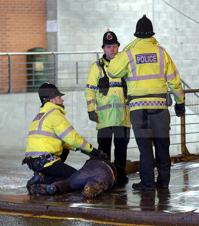 """© licensed to London News Pictures. Manchester, UK 17/12/2011. Police move a man in to recovery position and wait for an ambulance. Despite freezing temperatures, """"Mad Friday"""" revellers in Manchester enjoy what is traditionally the busiest night of the year for emergency services, before Christmas. Police rush to the aid of a man who has collapsed in the street as worried friends look on. Photo credit: Joel Goodman/LNP"""