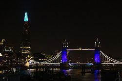 © Licensed to London News Pictures. 26/03/2020. London, UK. Tower bridge and the London Shard are illuminated in blue this evening in recognition and appreciation of National Health Service (NHS) staff working in hospitals across the country during the ongoing COVID-19 coronavirus epidemic. Photo credit: Vickie Flores/LNP