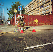 "This memorial has been placed where a young man called 'Clinton' died on the A1206 Manchester Road, London, England, UK. If we drove past this place where someone's life ended, the victim would just be an anonymous statistic but flowers are left to die too and touching poems and dedications are written by family and loved-ones. One reads: ""Your body is soft, not like street, Clinton."" From a project about makeshift shrines: Britons have long installed memorials in the landscape: Statues and monuments to war heroes, Princesses and the socially privileged. But nowadays we lay wreaths to those who die suddenly - ordinary folk killed as pedestrians, as drivers or by alcohol, all celebrated on our roadsides and in cities with simple, haunting roadside remberences."