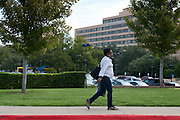 A woman walks towards Texas Health Presbyterian Hospital where Ebola patient Thomas Eric Duncan is said to have died on October 8, 2014, in Dallas. (Cooper Neill for The New York Times)