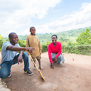 CAPTION: Jean Claude and Claudine try to brighten the day of a little boy, who is as poverty-stricken as they once were. When Jean Claude returned from Kigali, he and his sister were hosted by other families because government prescriptions on roofing did not allow them to live in their own thatch roofed house. Being hosted by others was not easy for them. While Jean Claude and Claudine were initially hosted without charge, later their hosts asked them to start paying. So the siblings moved into a rented home, and Jean Claude took up a lot of odd jobs in order to cover the rent. Often, he found it extremely hard work, and it remained difficult to cover the costs. Today, they are happy that their troubles are behind them, and they are looking forward to a positive future. LOCATION: Kabuga Village, Gafumba Cell, Rusatira Sector, Huye District, South Province, Rwanda. INDIVIDUAL(S) PHOTOGRAPHED: From left to right: Jean Claude Minani, Tite Hagenimana and Claudine Iradukunda.