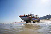 De reddingsboot van de KNRM (Koninklijke Nederlandse Reddings Maatschappij) in Noordwijk aan Zee wordt de zee in gereden.<br />