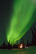 Alaska , Brooks Range. Iniakuk Lake Lodge. Northern Lights over a llit cabin in the Brooks Range at Iniakuk Lake Lodge.