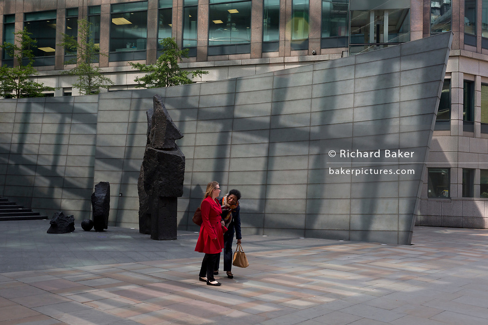 Women share a joke near modern architecture at Broadgate, on 10th May 2017, in the City of London, England.