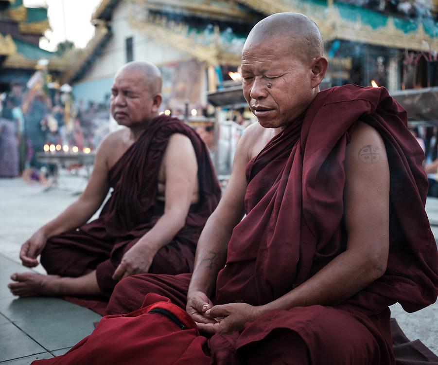 YANGON, MYANMAR - CIRCA DECEMBER 2017: Monks praying at the Shwedagon Pagoda in Yangon at night