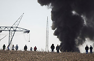 Spectators walk in a cornfield to get a better of view of the fire. A plume of smoke from an electrical fire at a station near North Liberty could be seen for miles.