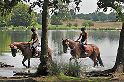 © licensed to London News Pictures. RICHMOND, UK.  02/08/11. Two horse riders walk their horses through water in order to cool them off. People and animals in the hot sun today (2nd August 2011) in Richmond Park, Surrey. Temperatures are set to reach 30 degrees Celsius in some parts of London over the next few days.  Mandatory Credit Stephen Simpson/LNP