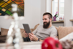 Young man using digital tablet and relaxing on sofa