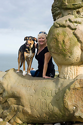 Attractive blonde older woman poses with her pet dog for photo Robin Hoods Bay